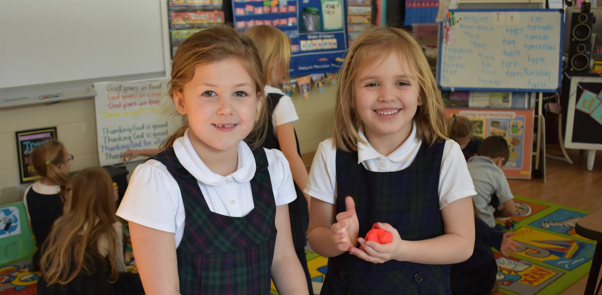 Two elementary school girls, one with a ball of red play dough