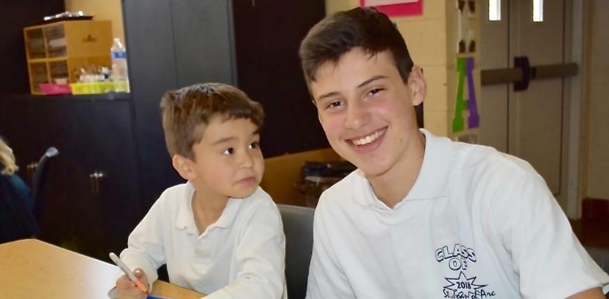 Eighth grade boy with his buddy student, a Kindergarten boy