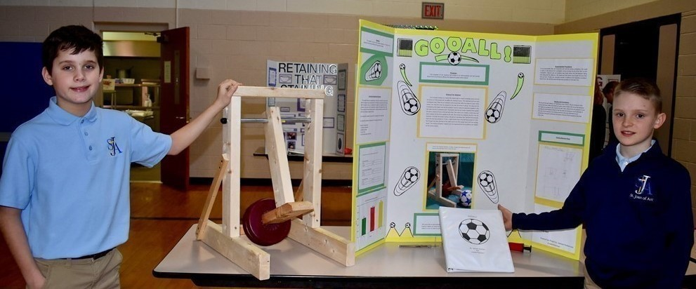 Two male students with their science fair project on kicking a soccer ball.