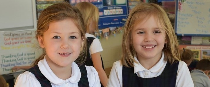 Two primary aged girls playing with play dough in school uniforms in a classroom