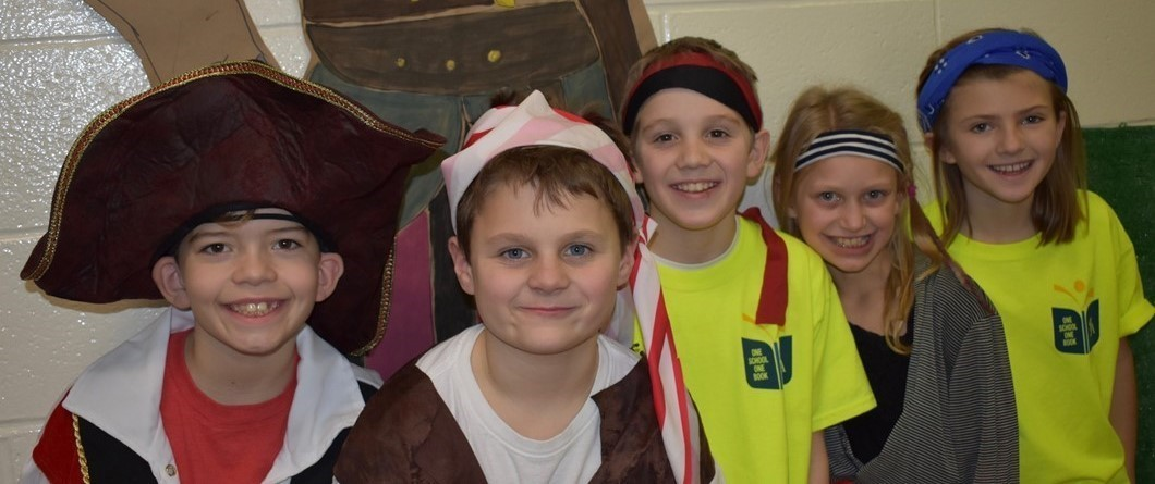 this is a picture of five students dressed as pirates. two girls in yellow shirts and three boys wearing pirate hats and bandanas