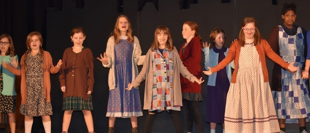 Student performance of Annie Jr. in association with Penguin Project. There is 9 girls on stage dressed like orphans.