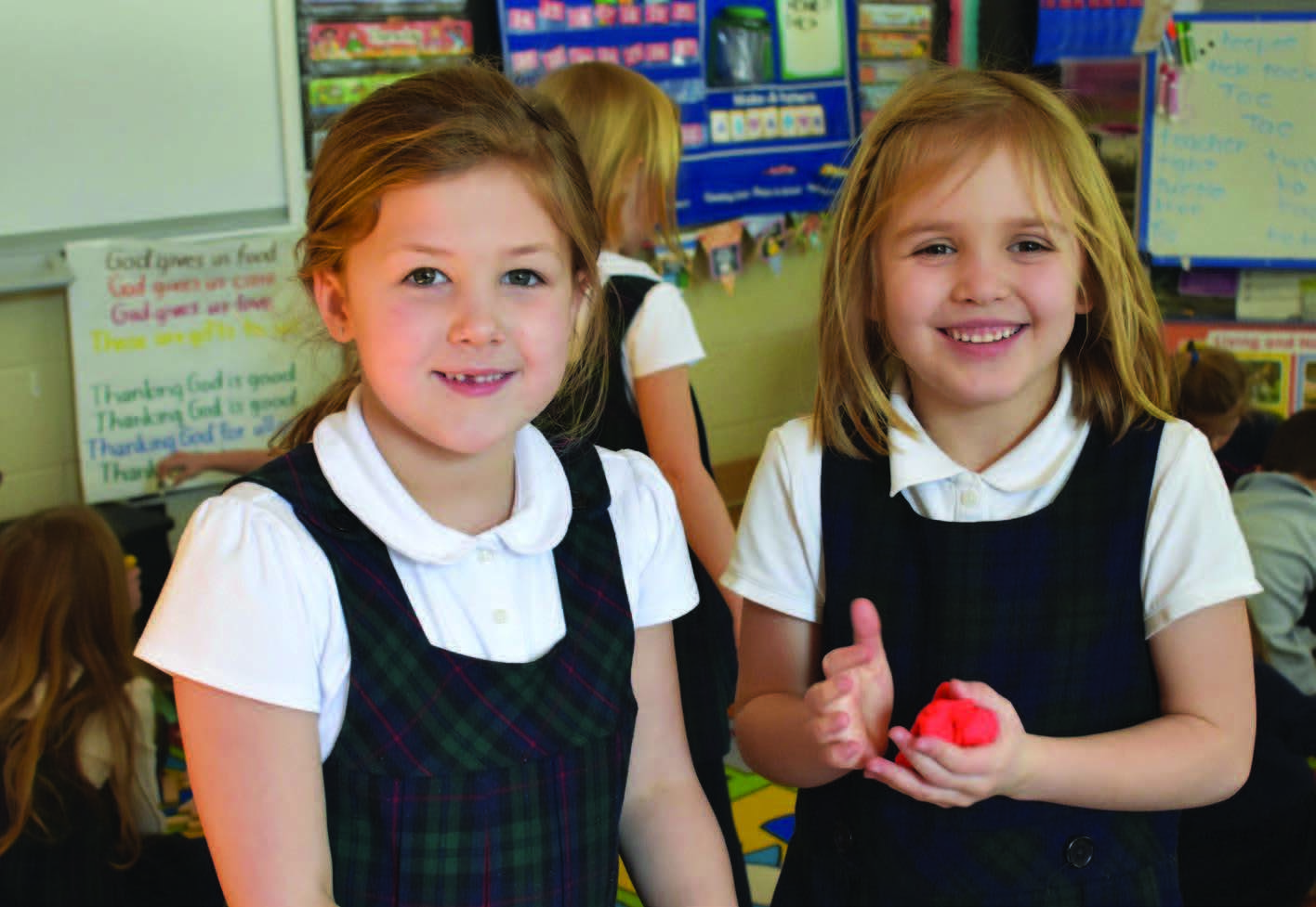 two young female students, one with red play-dough