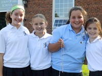 Four girls in SJA uniforms with a rosary outside in front of school.